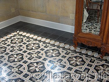 Black cement tile floor with sea shells and taupe