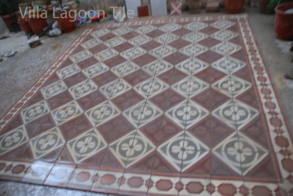 Cleaned ancient red, white and gray cement tile floor